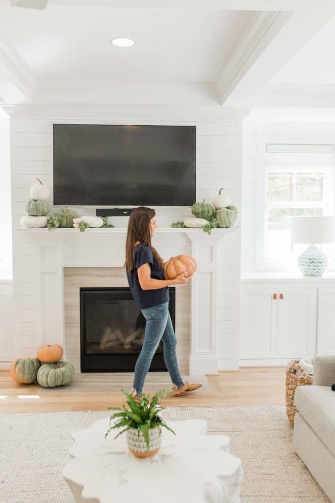 woman walking in living room holding pumpkin in front of fireplace