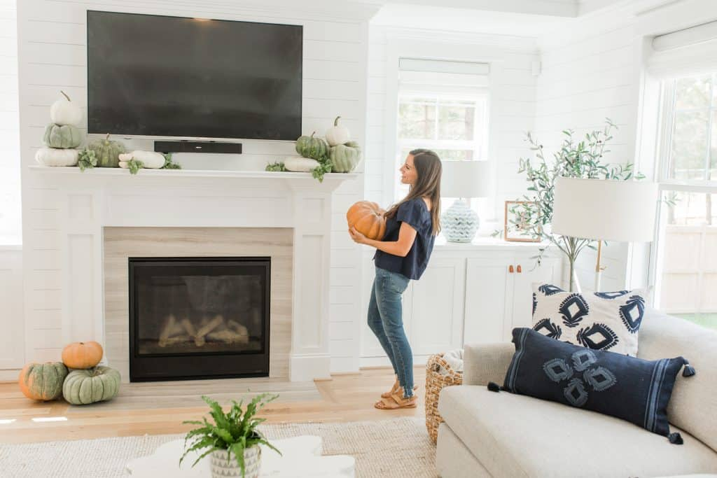 woman decorating mantel with a tv above it with pumpkins
