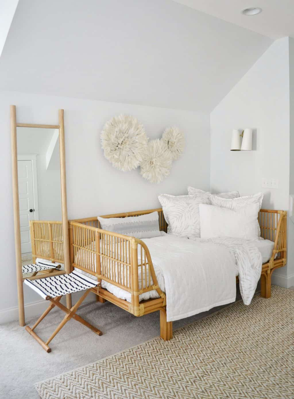 twin bed in guest room with juju hat on wall