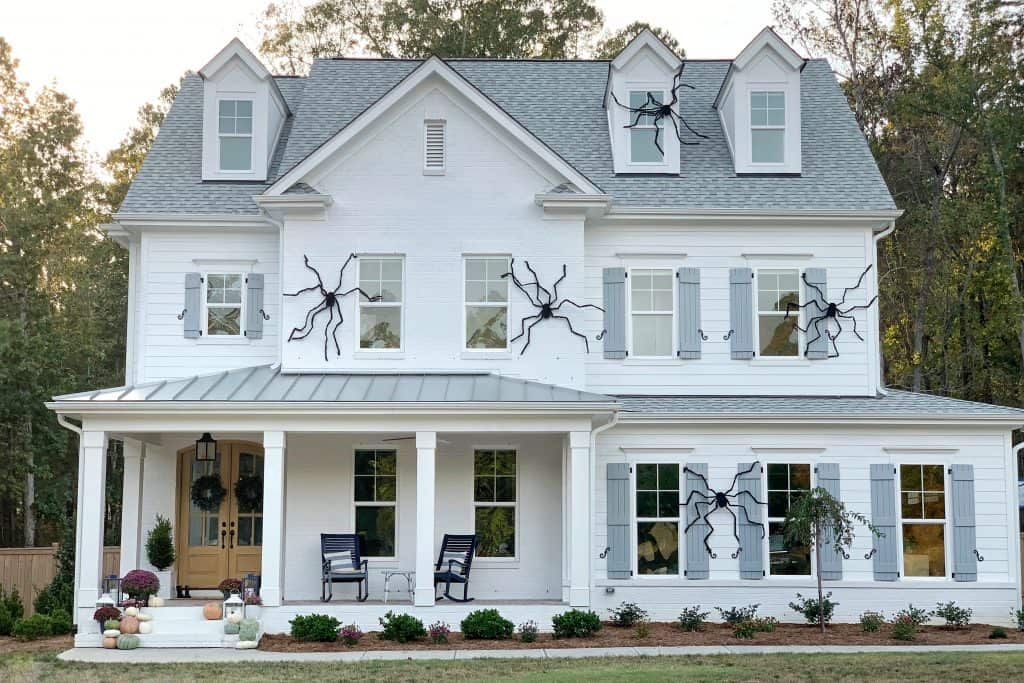 white brick home with giant halloween spiders on the front