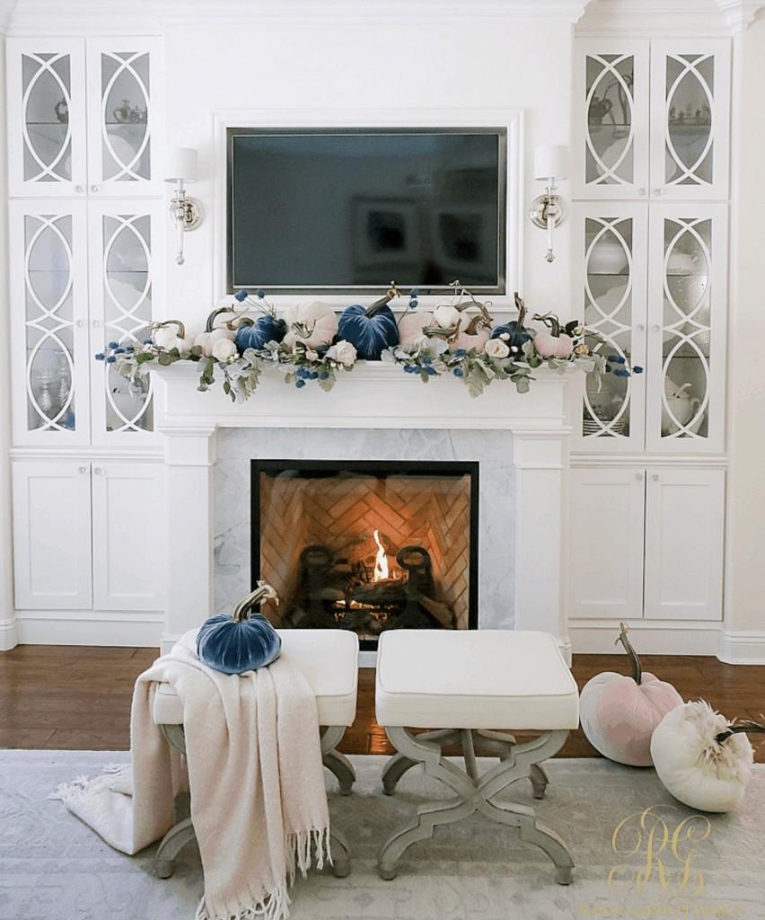 mantel with pumpkins and sconces above fireplace