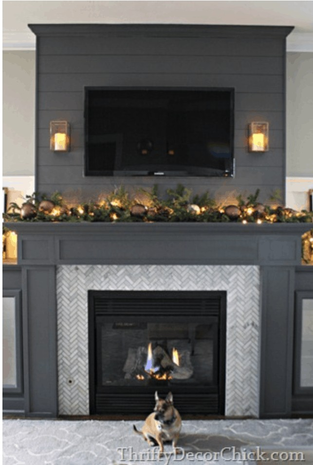 TV styled with decor underneath it on a mantel