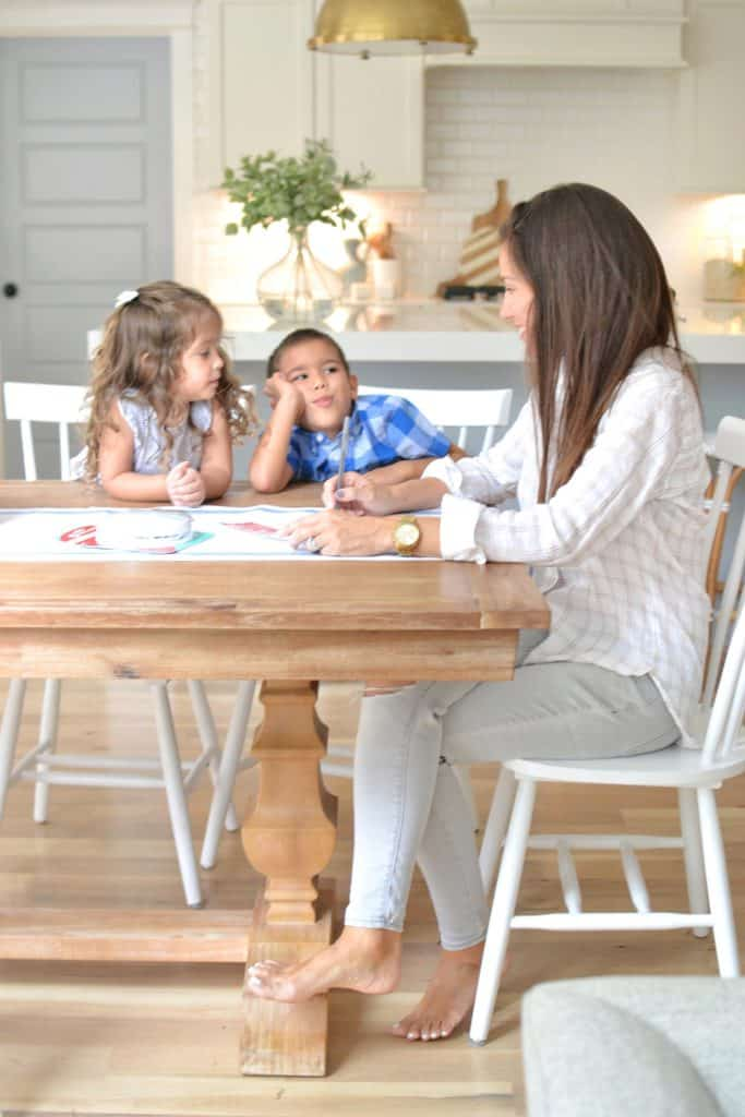 a mom sitting with kids at table with a pen and paper