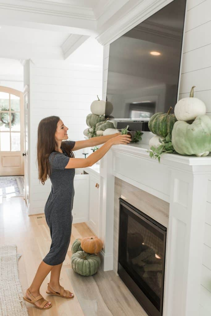 woman decorating her mantel under a tv