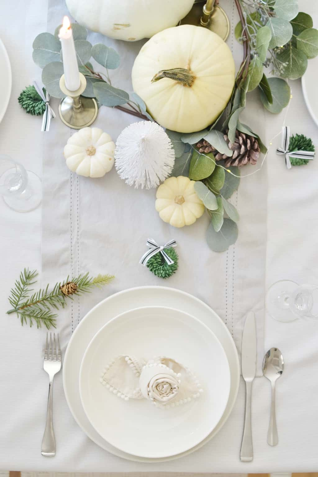 a plate on a table with candle, pumpkins and christmas tree