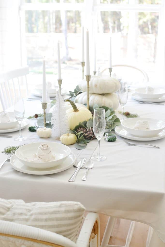rose napkin fold sitting on a plate on a modern christmas table