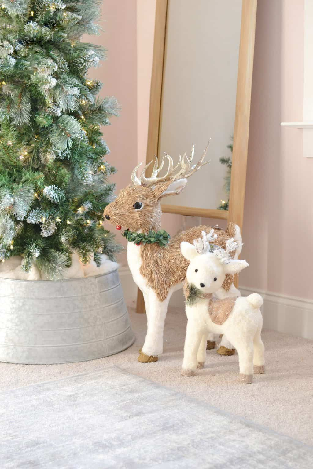 2 sparsely deer under a christmas tree in the girls room