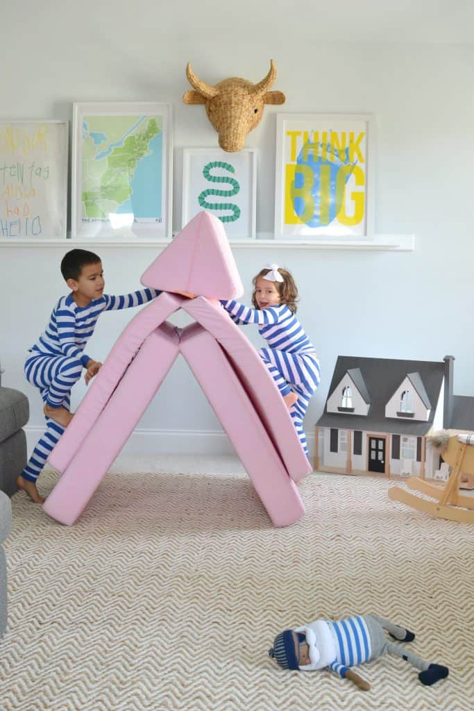 playroom with 2 kids climbing up a Nugget Couch
