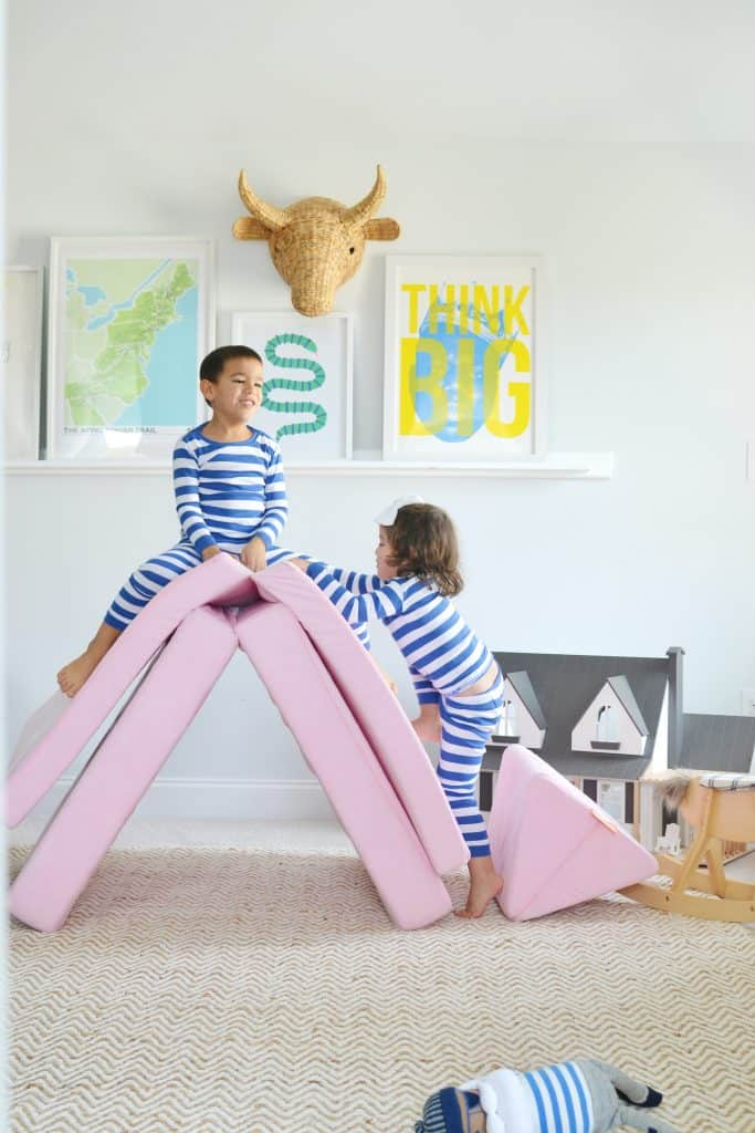 2 kids playing on a nugget couch in a playroom