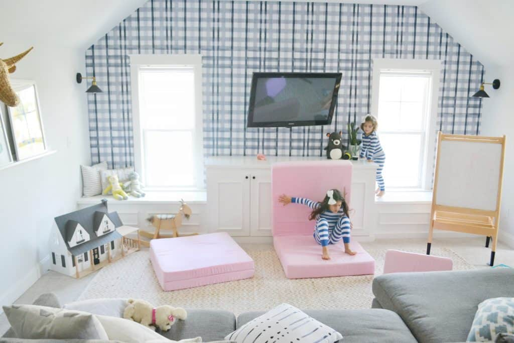 girl jumping in a playroom on a nugget couch