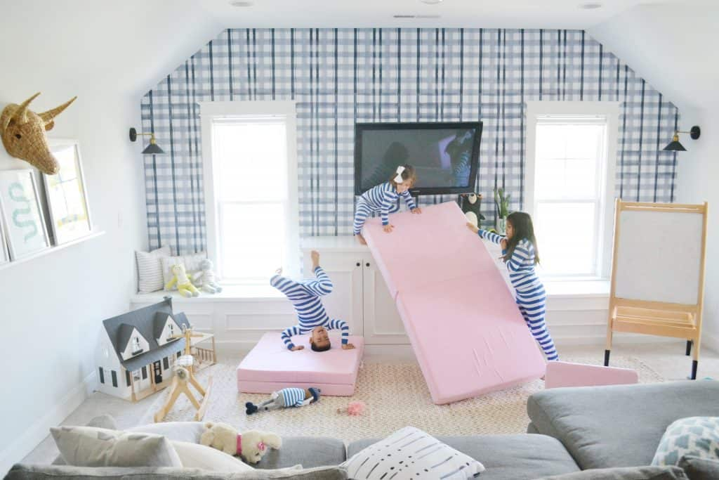 playroom with 3 kids doing handstands on a nugget couch