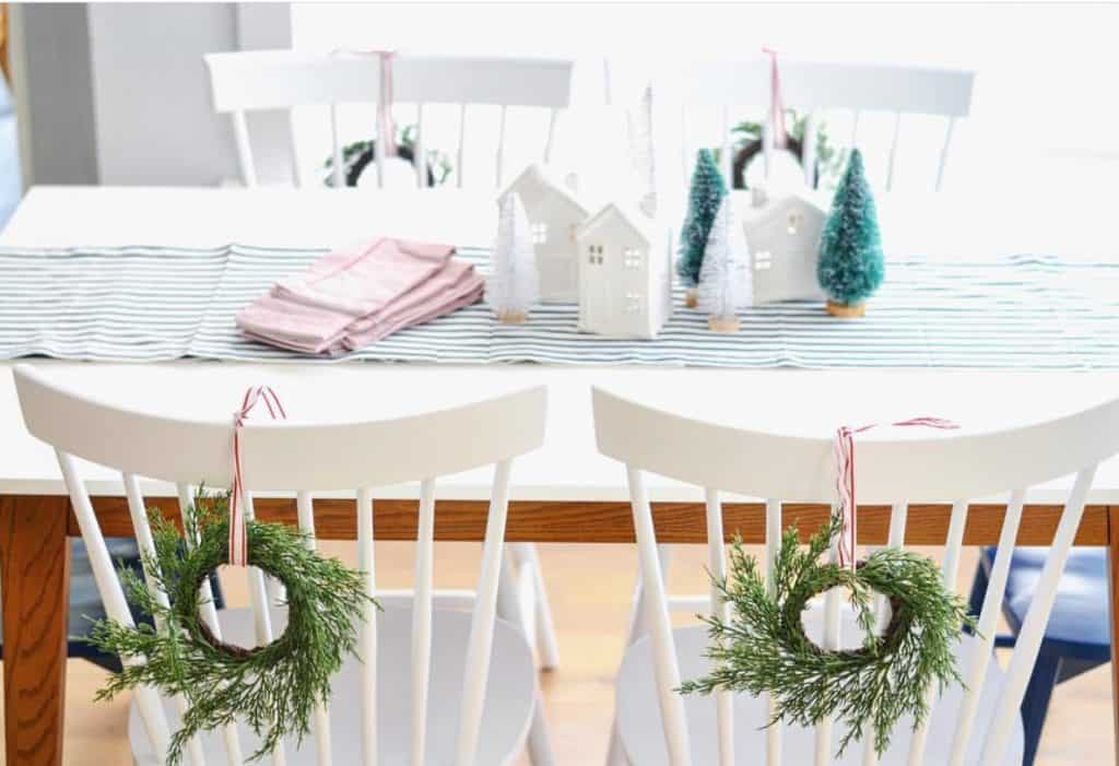 table decorated for Christmas with white chairs and wreaths on the back