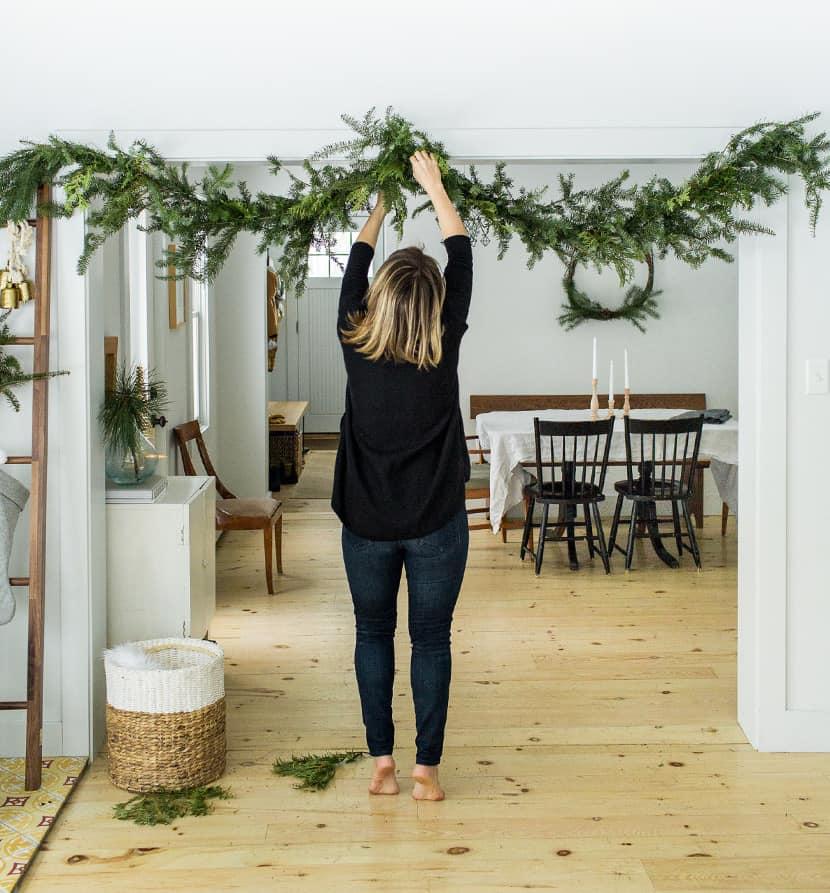 girl putting up garland over doorway