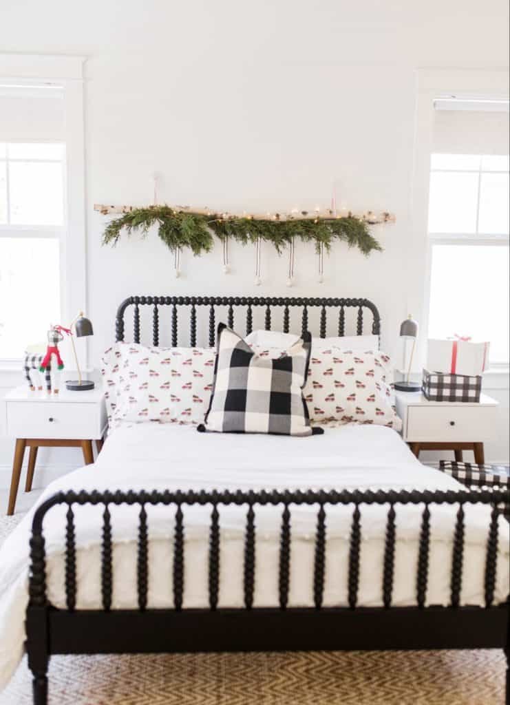 black bed with a birch log wall hanging above it