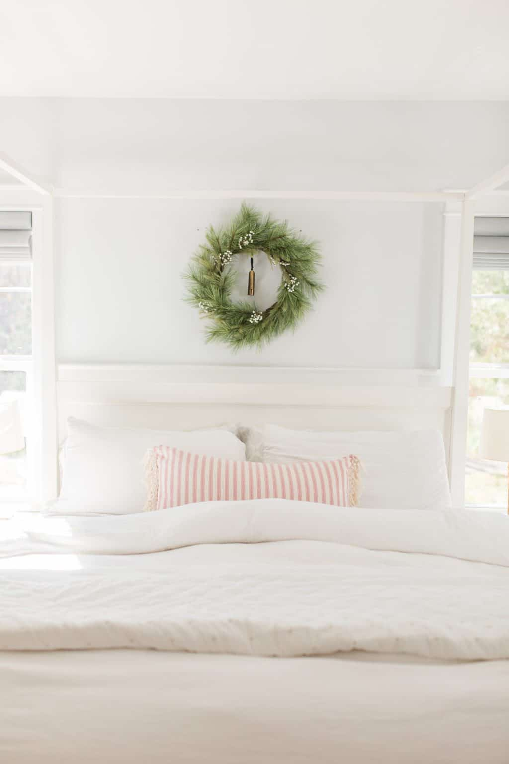 christmas wreath above a canopy bed in a bedroom