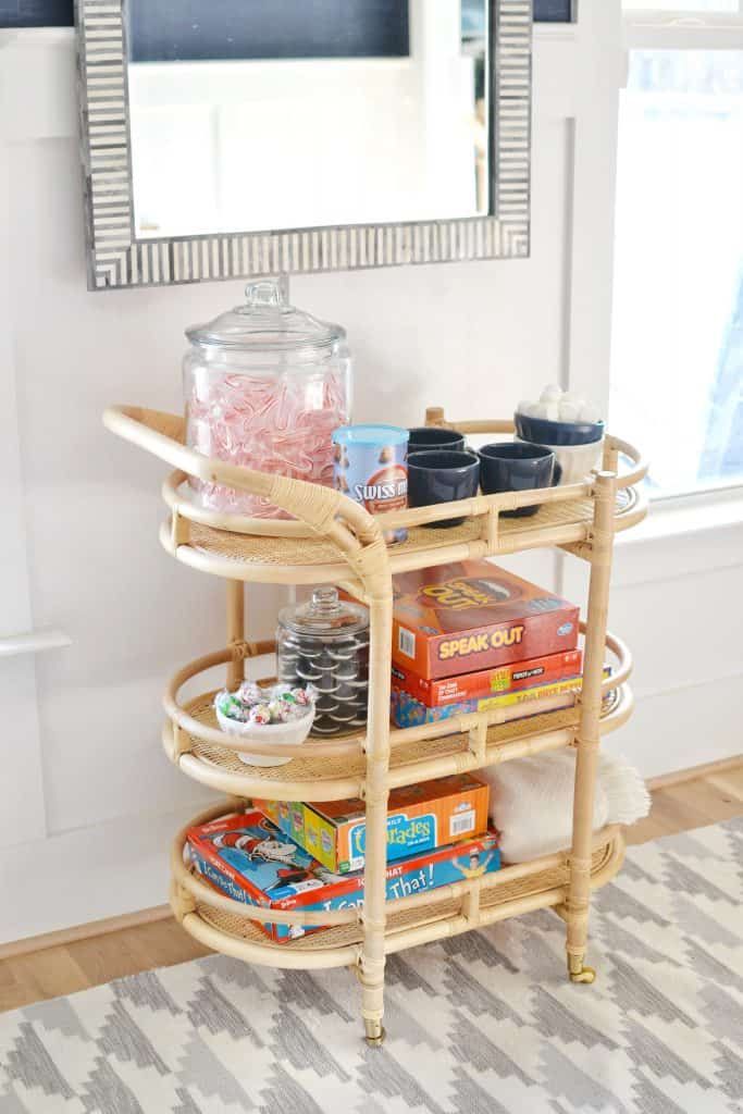 bar cart under a mirror with games and sweets