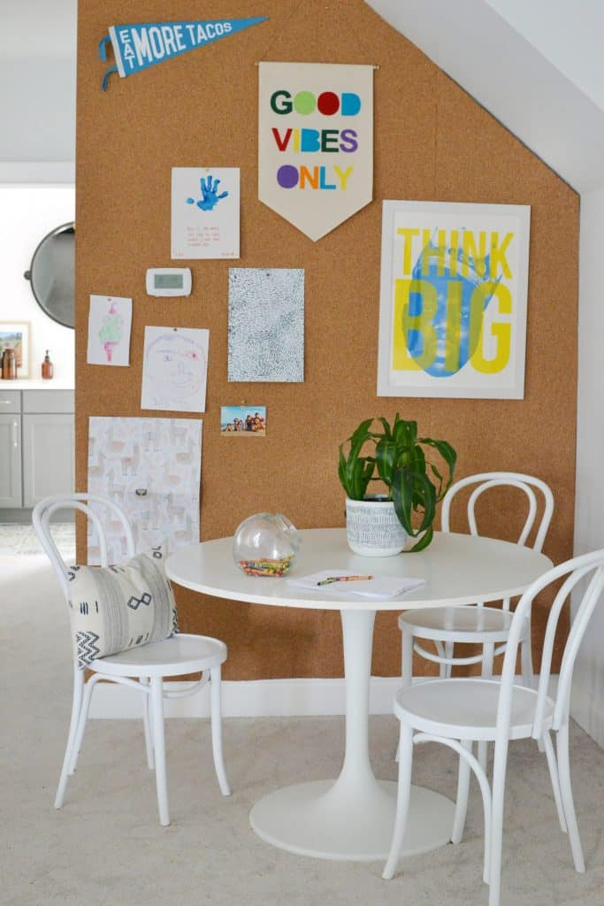 Cork board wall with white table and chairs
