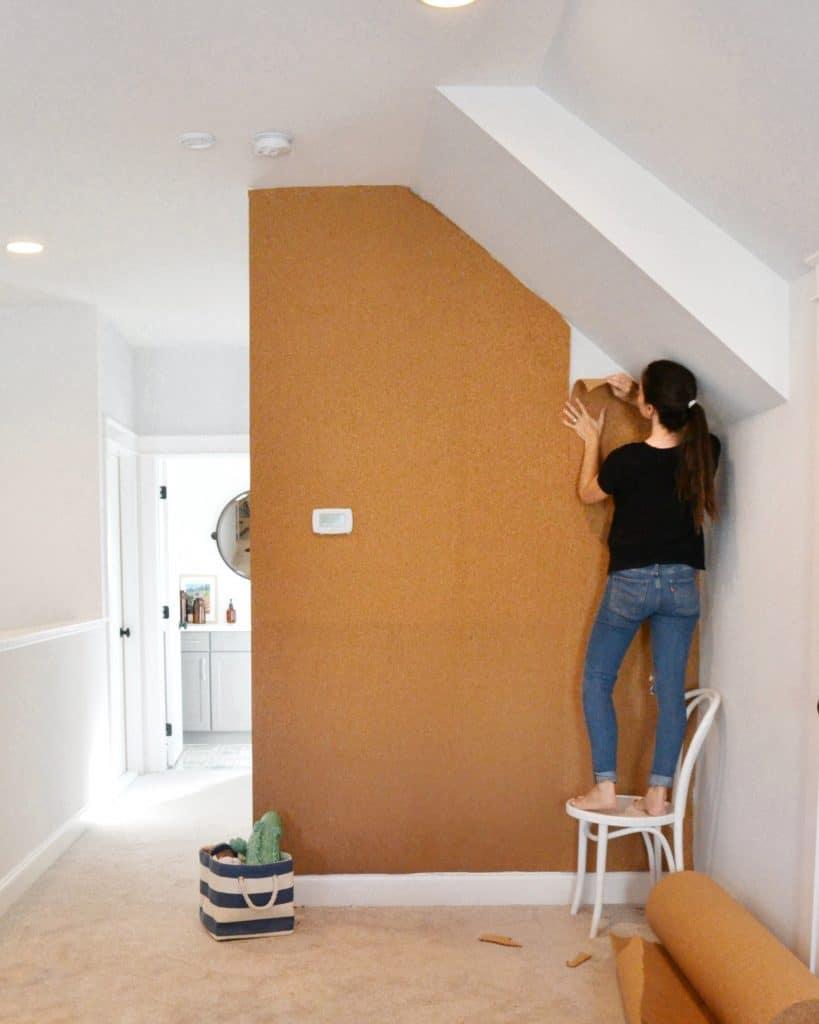 woman installing a cork board wall
