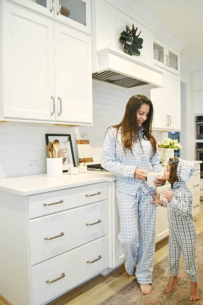 mom in blue gingham pajamas and a child in kitchen
