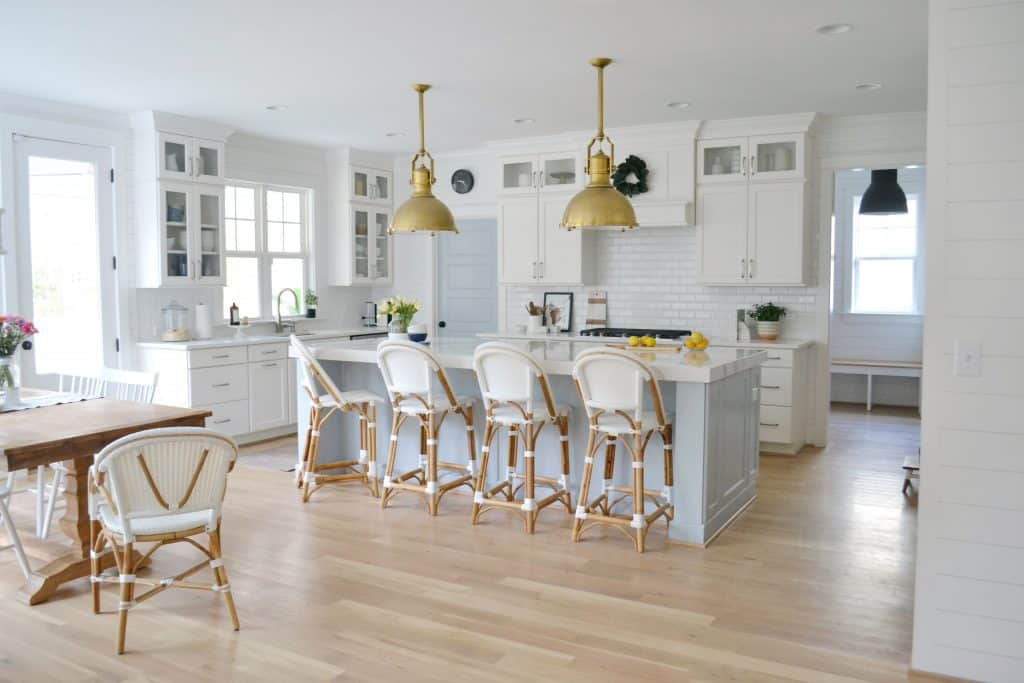 kitchen island with 4 riviera barstools and industrial pendant lights hanging over the island