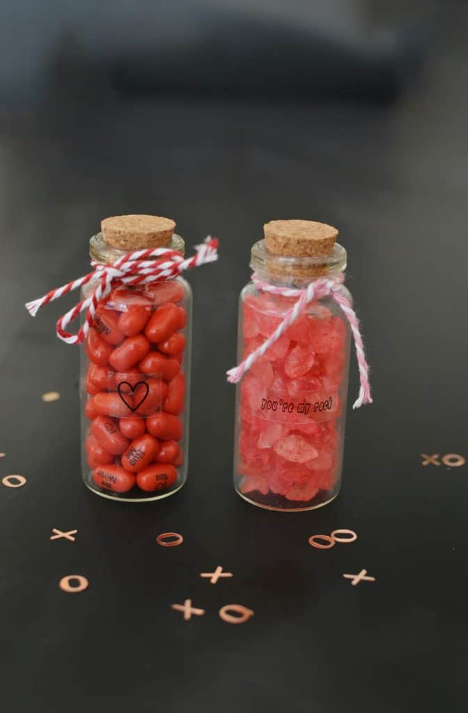 2 mini bottles of candy with ribbon around it