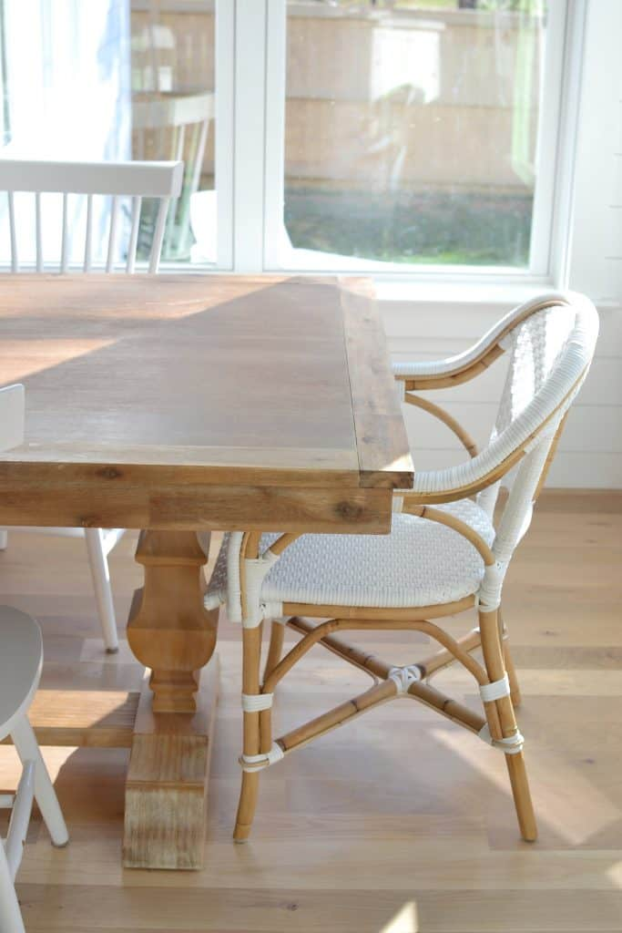 bradding table in a kitchen with white chairs around it