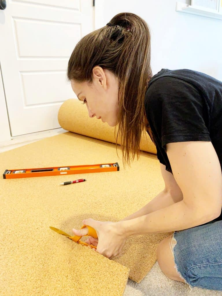 Girl cutting a large cork roll with scissors for the cork board wall