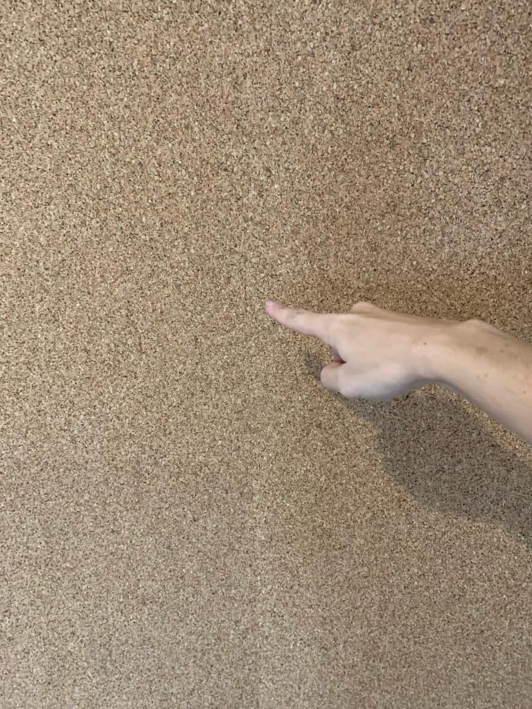 2 rolls of cork board with a finger pointing to the seam