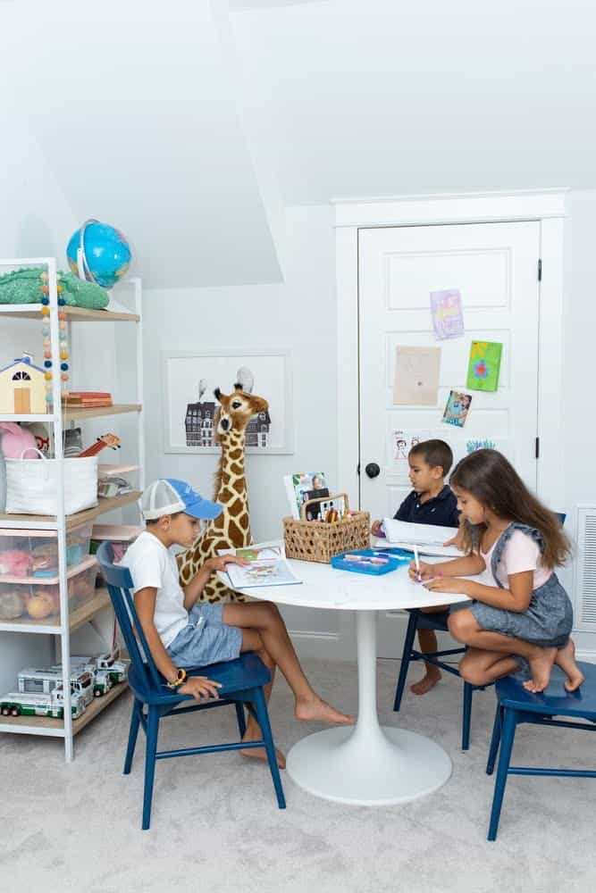 3 kids sitting at a game table in a playroom