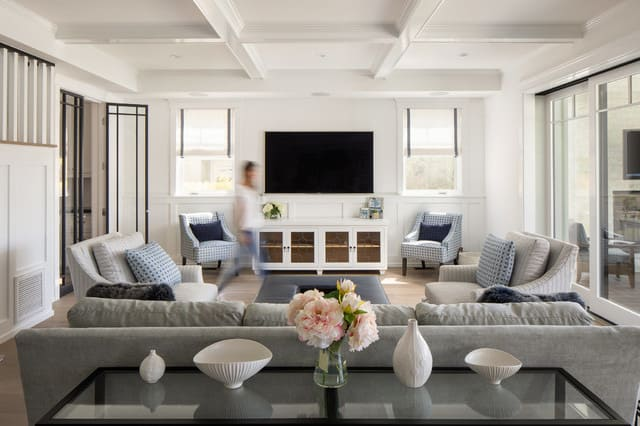 white living room with a woman walking across it