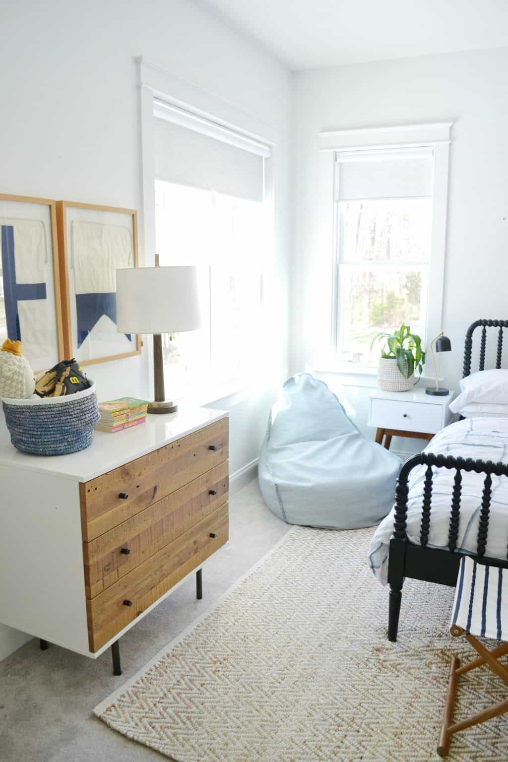 a corner of a bedroom with a dresser, a basket of toys and a bean bag chair