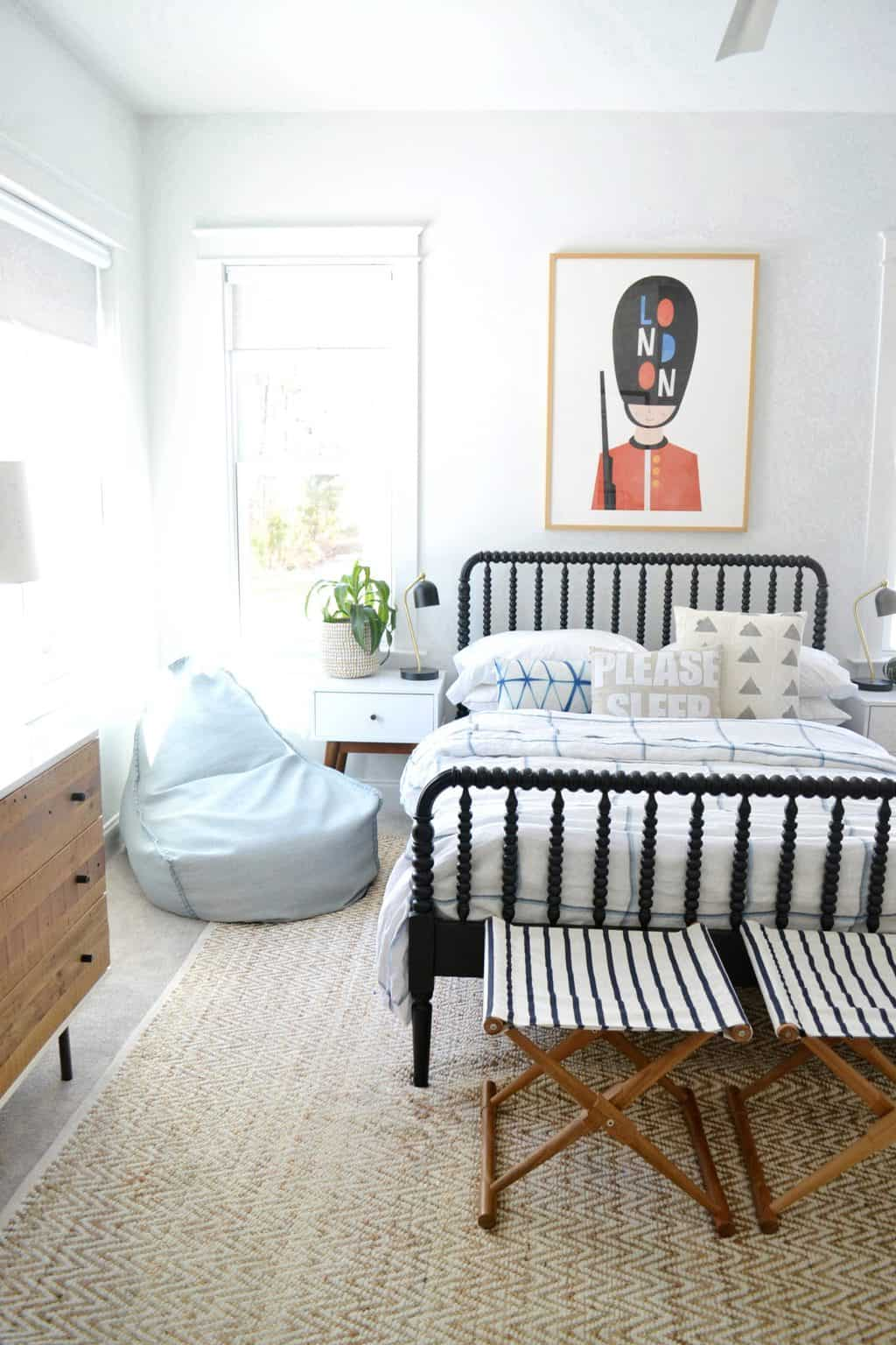 bedroom with a bean bag chair and large art behind bed