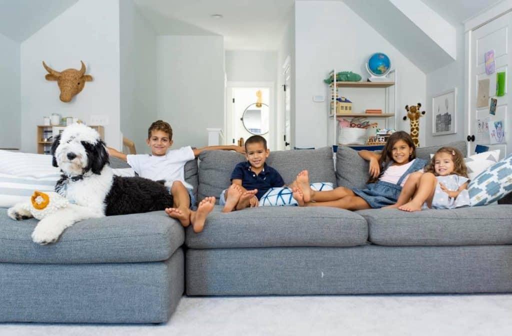 4 kids on a sofa with a sheepadoodle