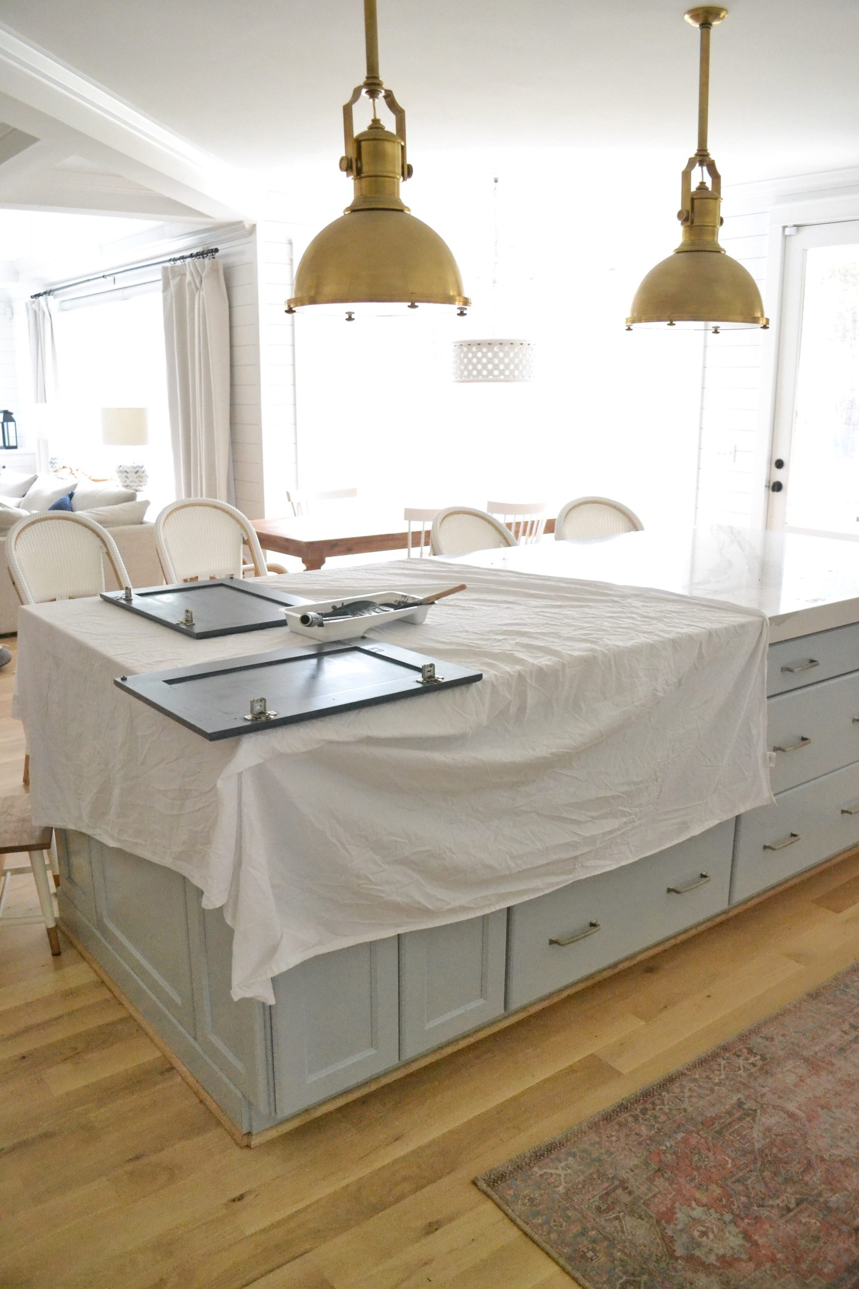 kitchen covered in sheets with painted bathroom cabinet on top