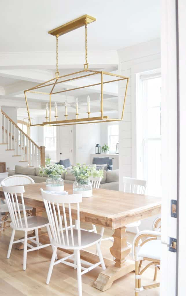 Visual Comfort Darlana linear pendant in a kitchen over a table with white chairs