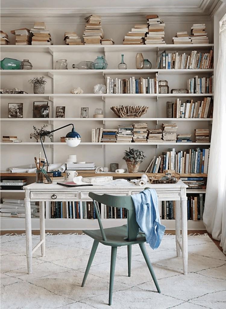a white feminine desk with built in bookshelves behind it