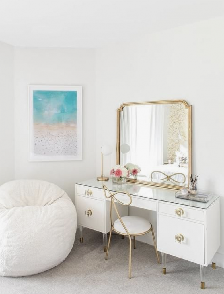 white and brass desk with a mirror above it