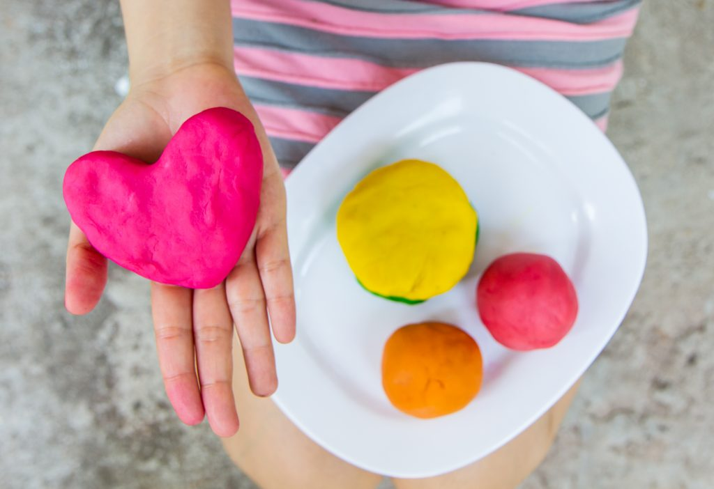 kid holding heart shaped play dough activities for kids