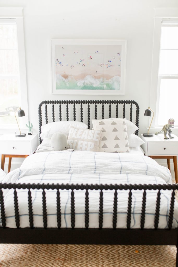 black bed and a Gray Malin print above it in a guest bedroom