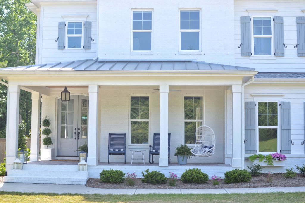 white front porch with hanging chair