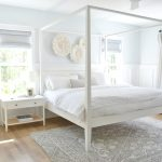 white canopy bed in a neutral bedroom