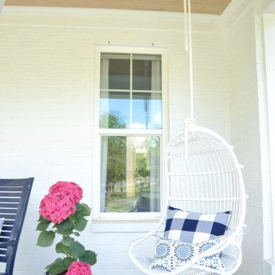 outdoor white chair hanging on a rope with a pillow