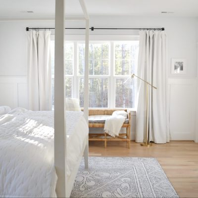 shore bench in a neutral, white bedroom with big windows