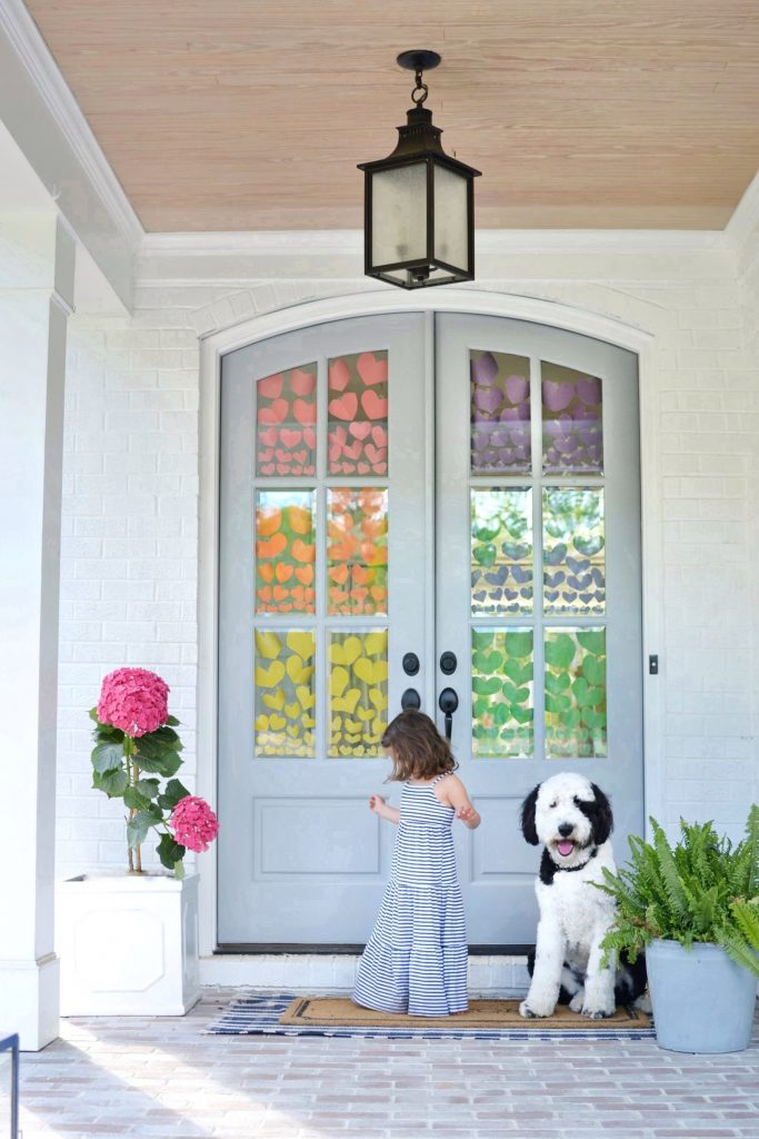 a rainbow of hearts in the windows of a blue door on a porch