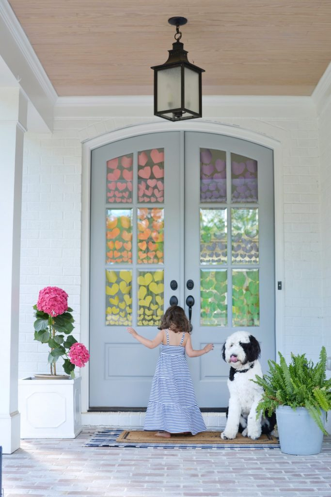 front porch with a rainbow of hearts on front door windows