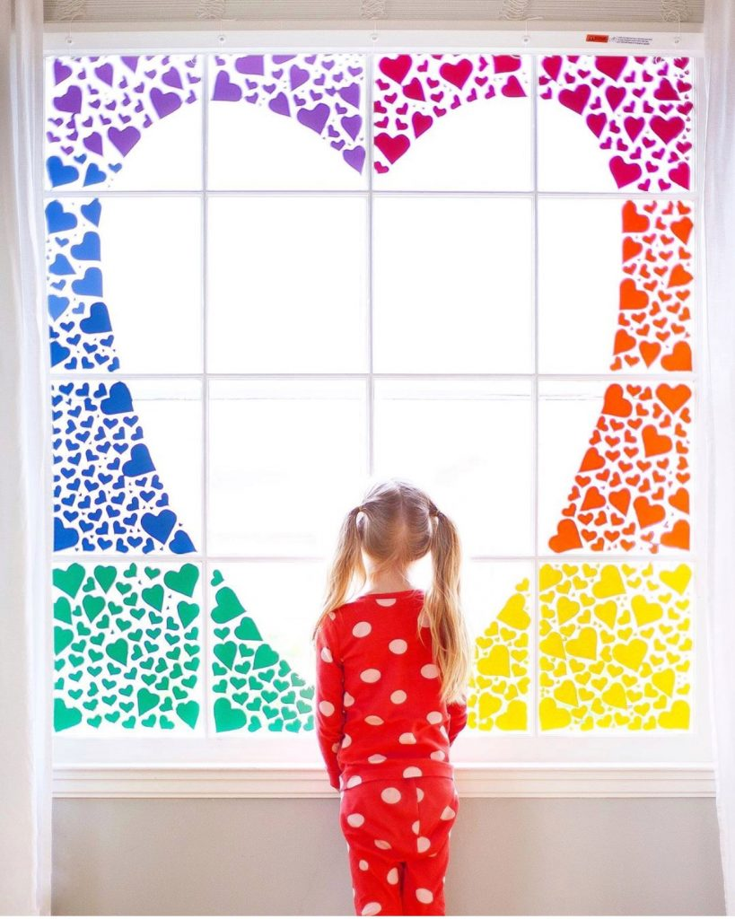 rainbow hearts on a window with a girl in front