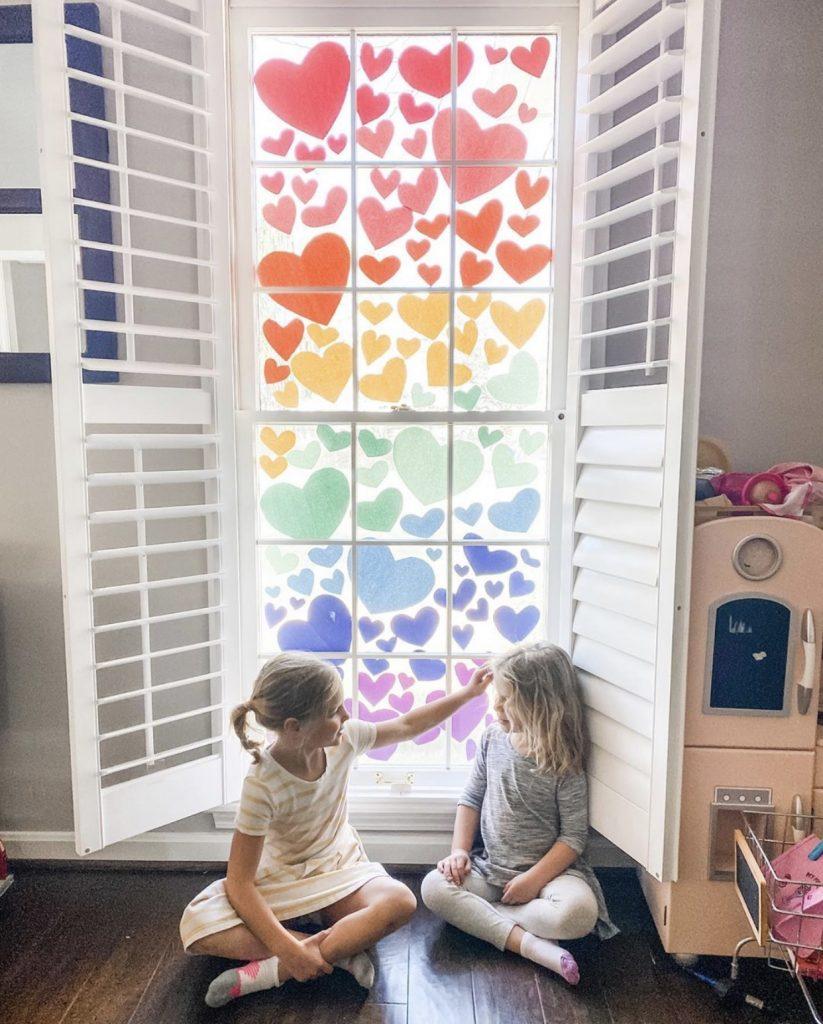 2 little girls in front of a window talking