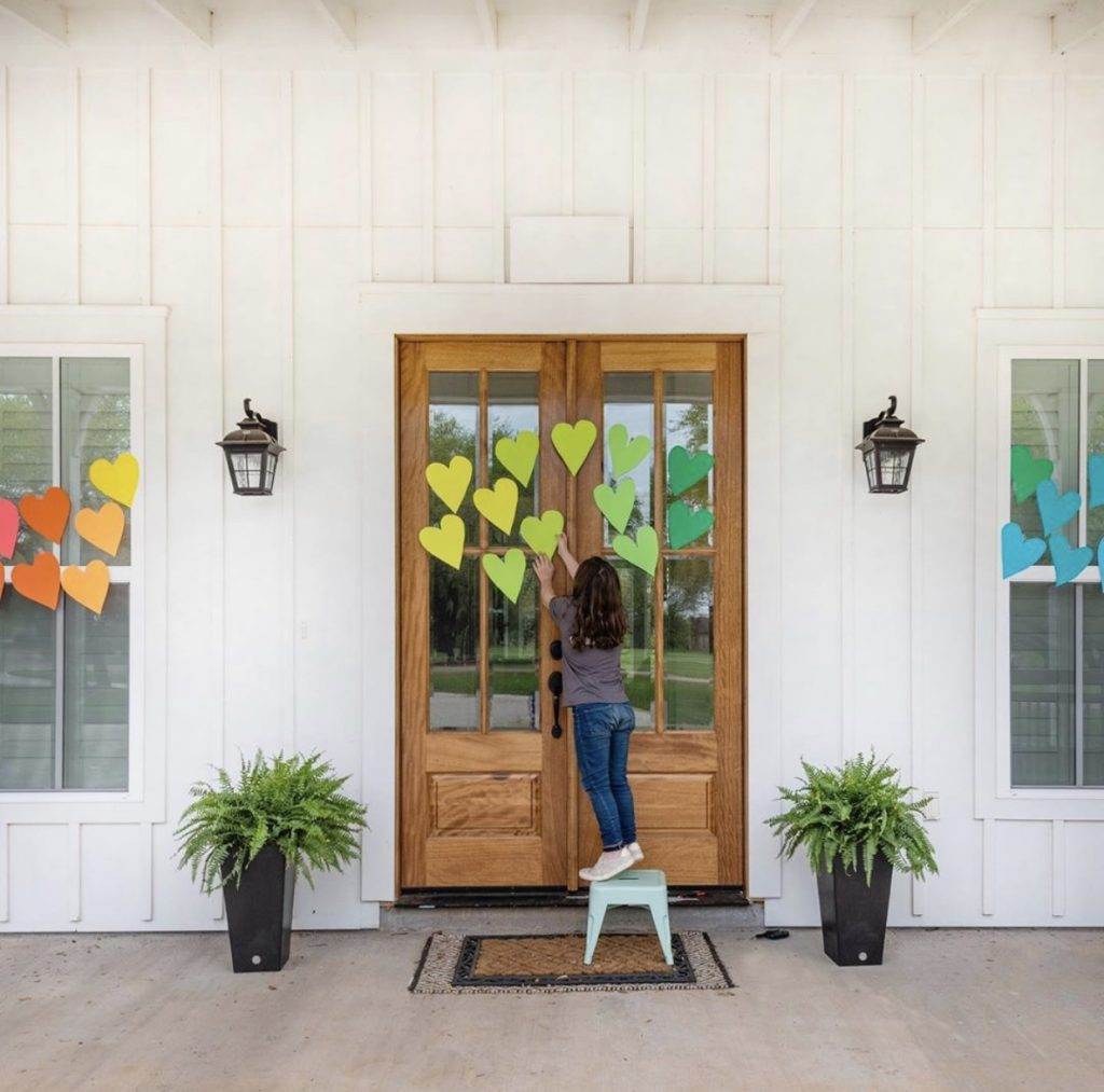 girl in front of wood doors decorating the windows