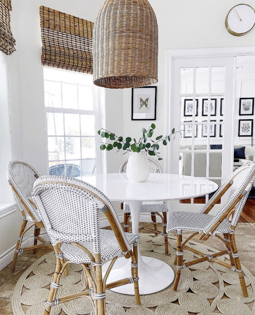white round dining table in a kitchen nook with rattan