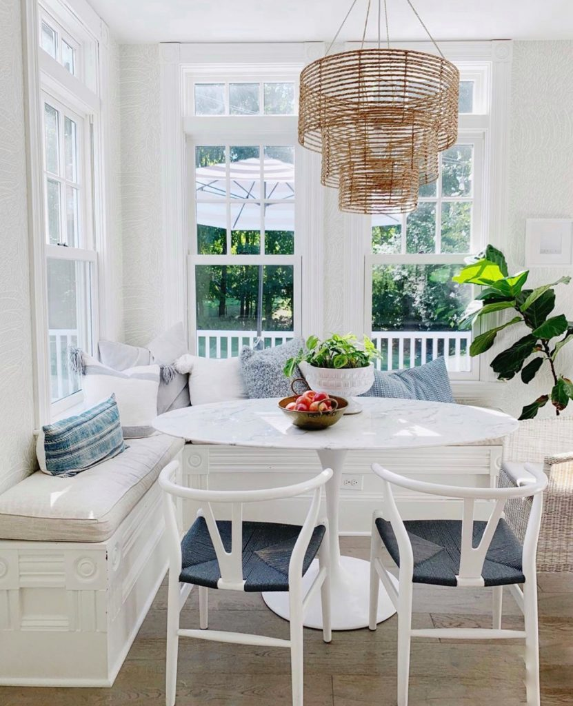 white kitchen table in a nook with big windows